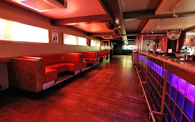 A long bar at Bridge, Oxford, to a backdrop of red light