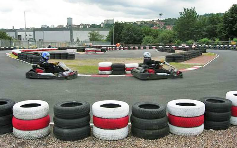 Two karts racing on an outdoor karting track, with tyres lining the edge of the circuit