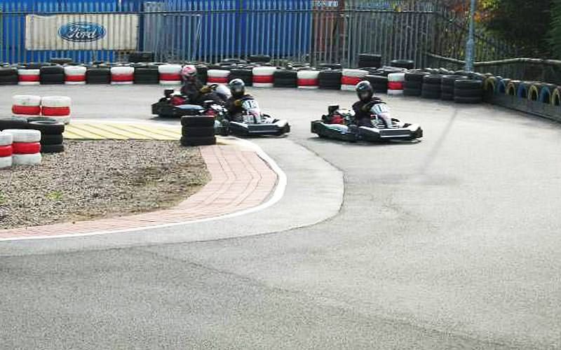 Three karts racing on an outdoor karting track, with tyres around the edges of the circuit