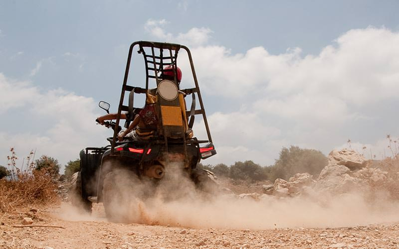 The rear of an off-road buggy being driven down a dirt road