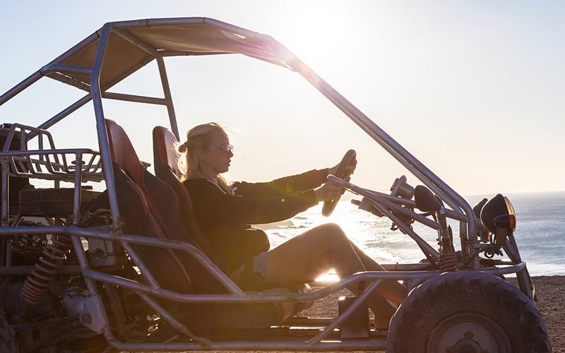 A woman sitting in an off-road buggy, viewed from the side with the sea in the background