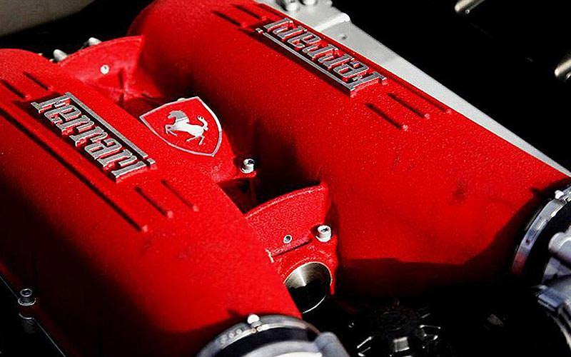 A close up of a red Ferrari car engine