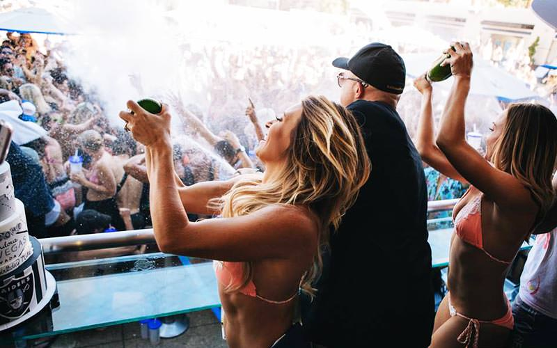 A man and two bikini-clad women spraying champagne off a balcony