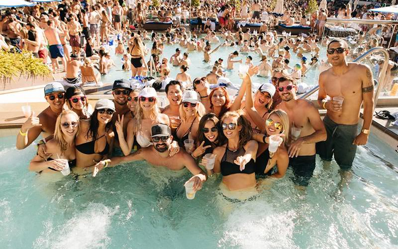 A group of people posing in a swimming pool at Wet Republic