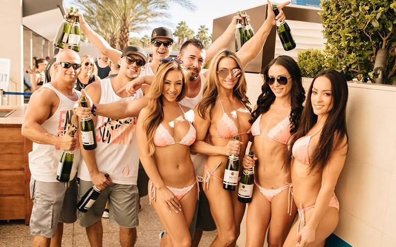 A group of men and women posing with bottles of champagne