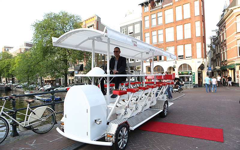 Men and women sat on a white beer bike with a building in the background