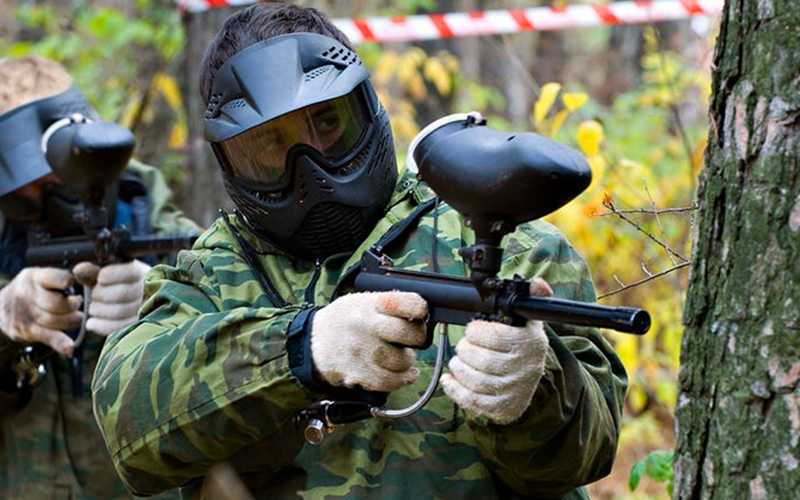 A man in a camouflage suit and a paintball mask aiming a paintball gun