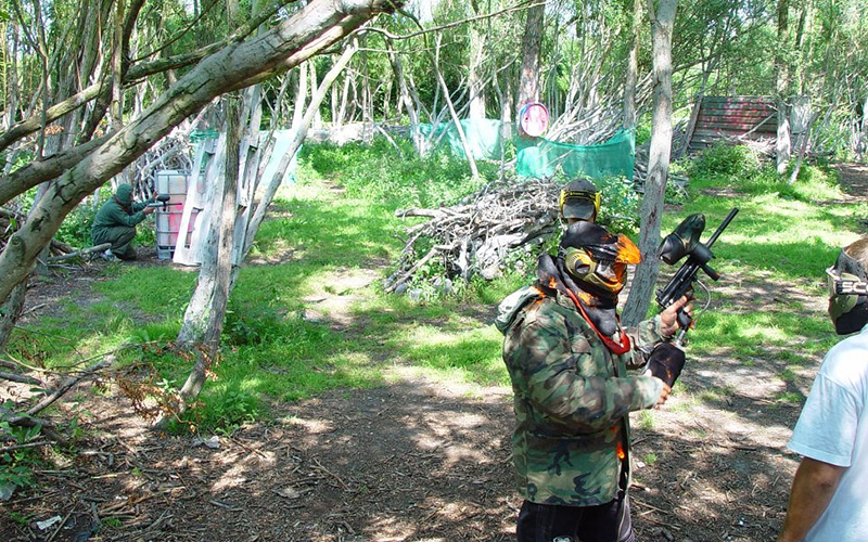 A man on a paintball field talking to a marshal