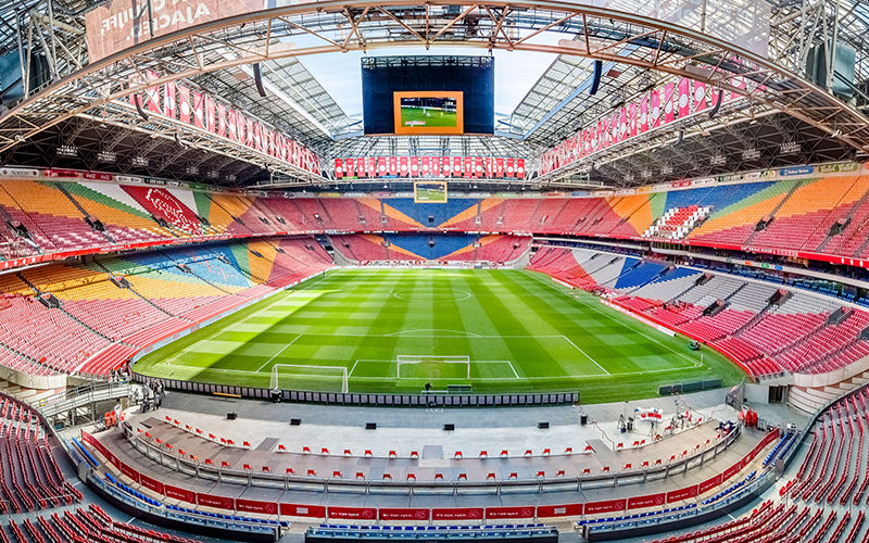 A man and woman sat in the spots of two players in the Ajax stadium changing rooms