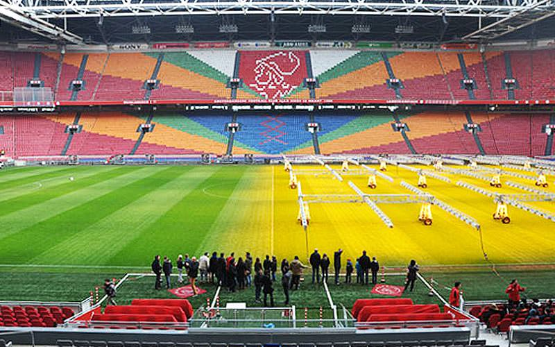 The seats and pitch at Ajax Stadium, with a crowd of people at the side of the pitch