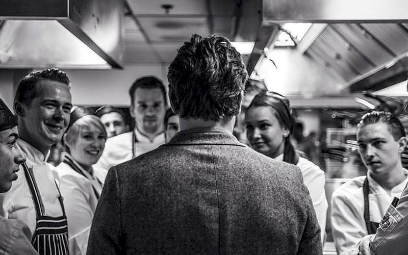 Black and white image of the back of a man talking to a group of chefs in a kitchen