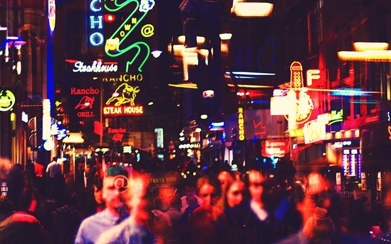 Lots of people walking under neon signs in Amsterdam