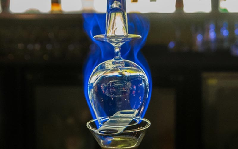 A cocktail glass surrounded by a blue flame