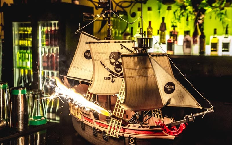 A pirate ship on a bar, with a sparkler coming out of a cannon