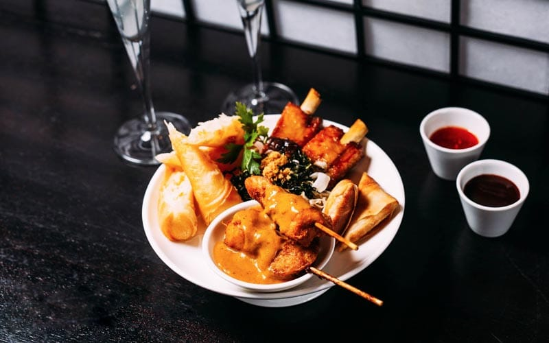 An Asian-inspired sharing platter, with two bowls of sauce next to the plate