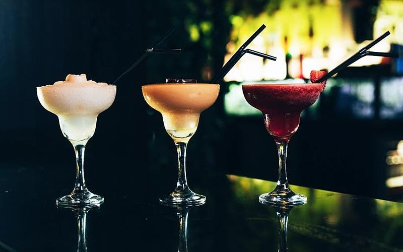 Three cocktails lined up on a bar