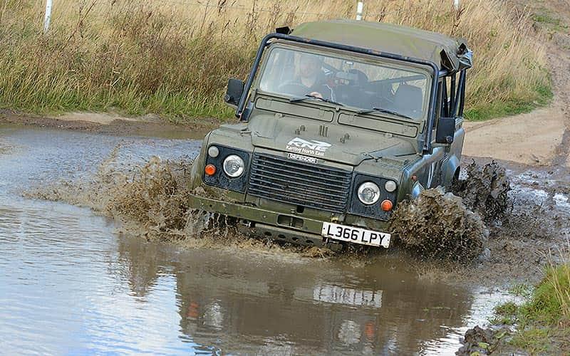 A man driving a 4x4 through a muddy puddle