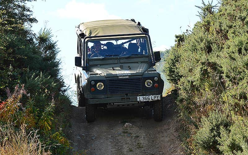 A man driving a 4x4 through a mud path, with trees on either side