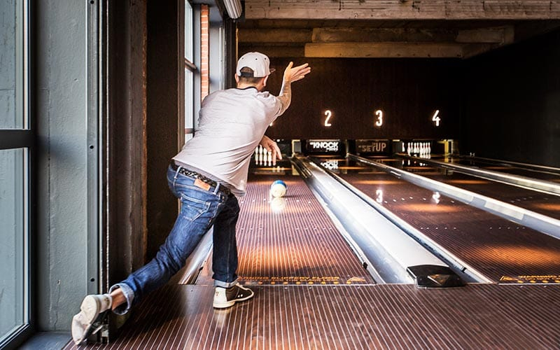 Guy in jeans and white t-shirt bowling