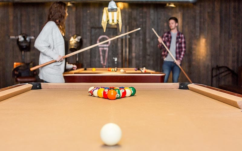 Pool table set for break with two people playing in the background