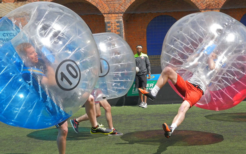An inflatable zorb next to a football, on a pitch