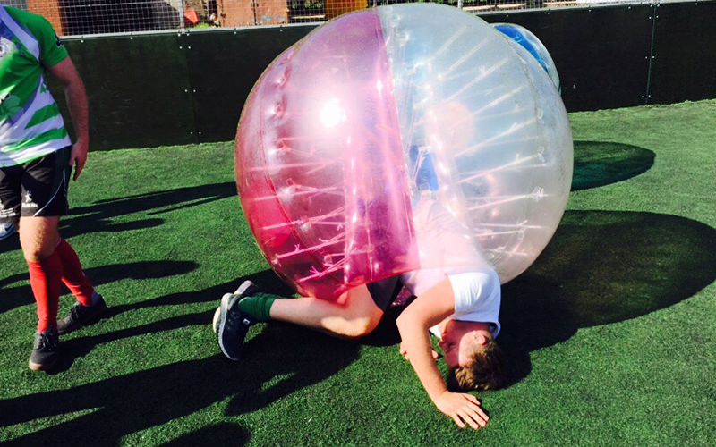 Four men playing in inflatable zorbs on a field