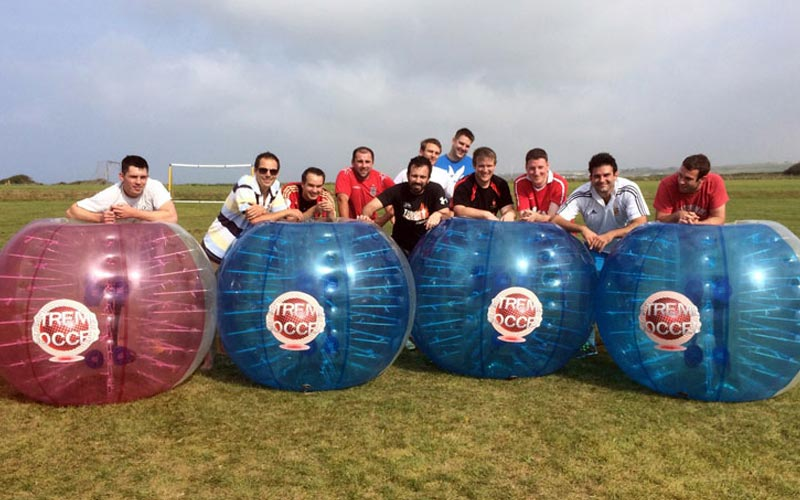 A group of men around inflatable zorbs
