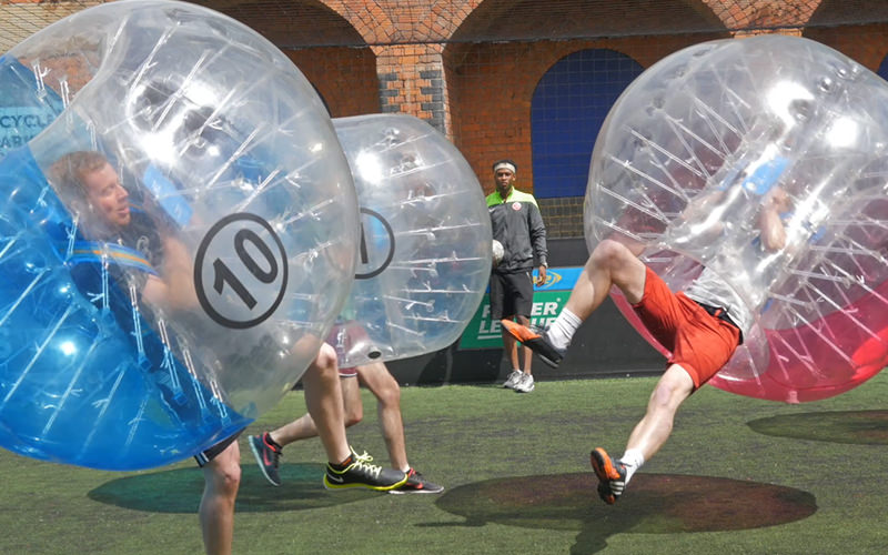 Two people in zorbs bouncing off each other while playing bubble football
