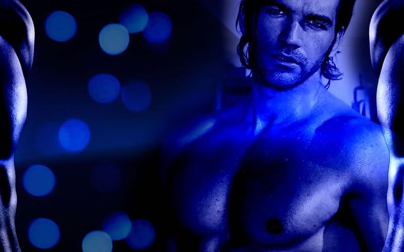 A topless man posing under blue lights