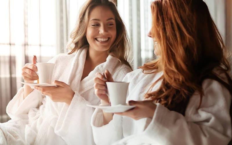 Two women drinking tea in white dressing gowns
