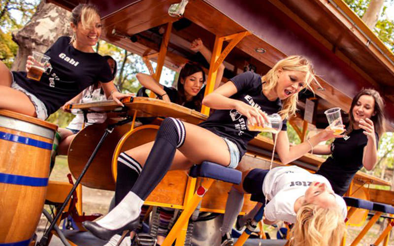 Women sat on beer barrels on a beer bike, with one woman pouring beer on another one bending backwards