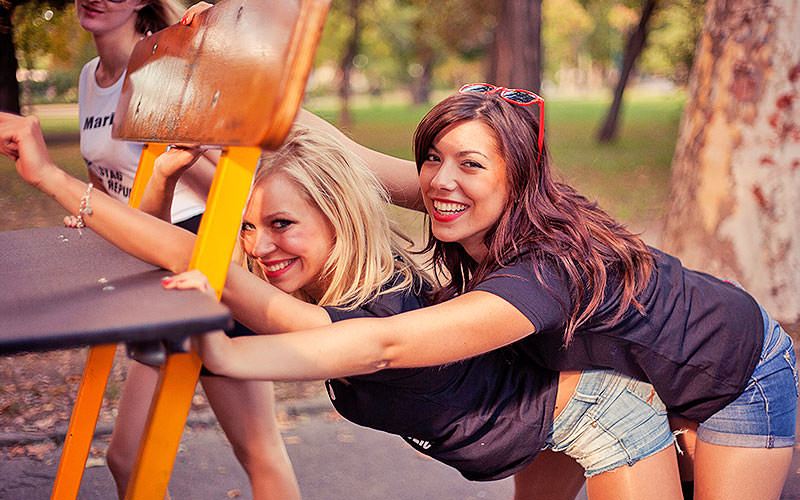Two women bending forwards and posing whilst clinging onto a seat on a beer bike