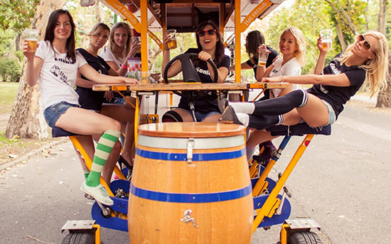 Women sat on a beer bike and posing whilst holding cups in the air, with a woman steering the bike in the middle