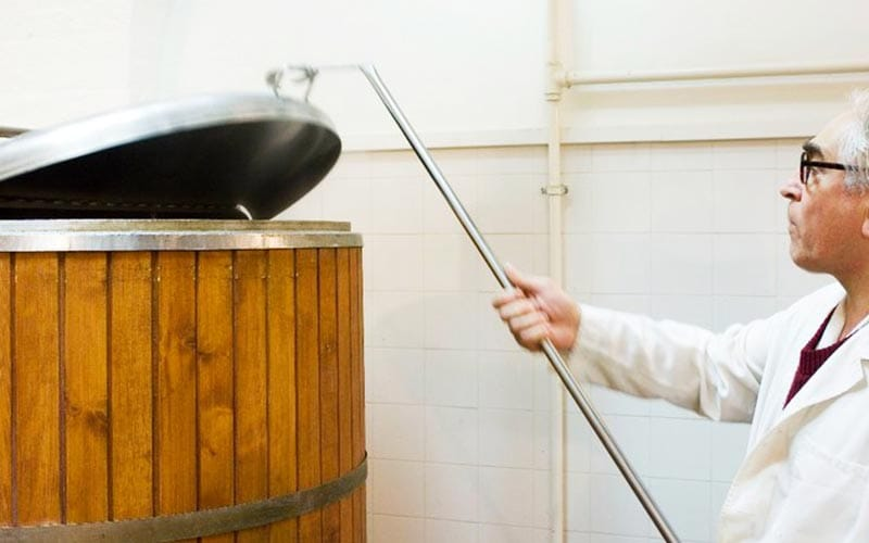 A brewer pulling the lid off a vat