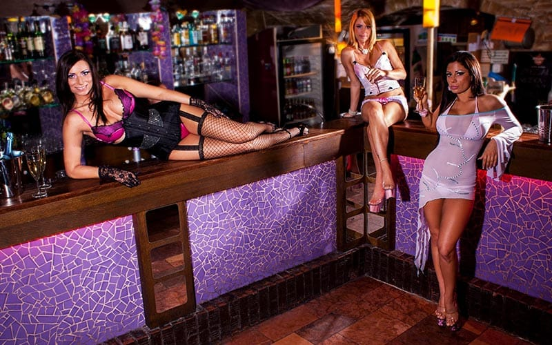 Three strippers in 4Play Lounge, lounging around the bar area