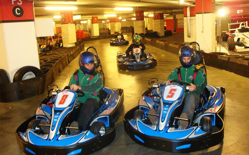 Some people driving around in go karts on an indoor track