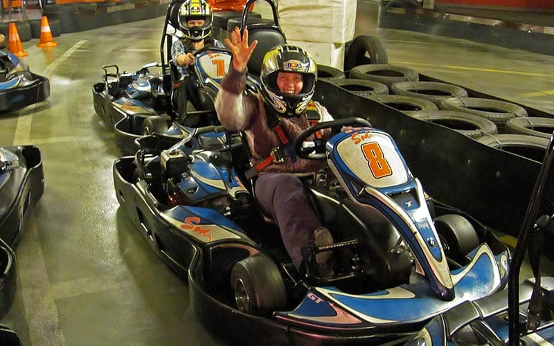 Some men in go karts holding their hands up to the camera