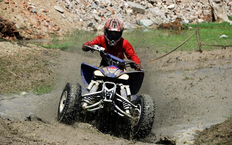 A man riding a quad bike through a dirt track