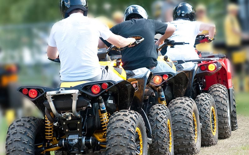 Three men riding quad bikes in a line