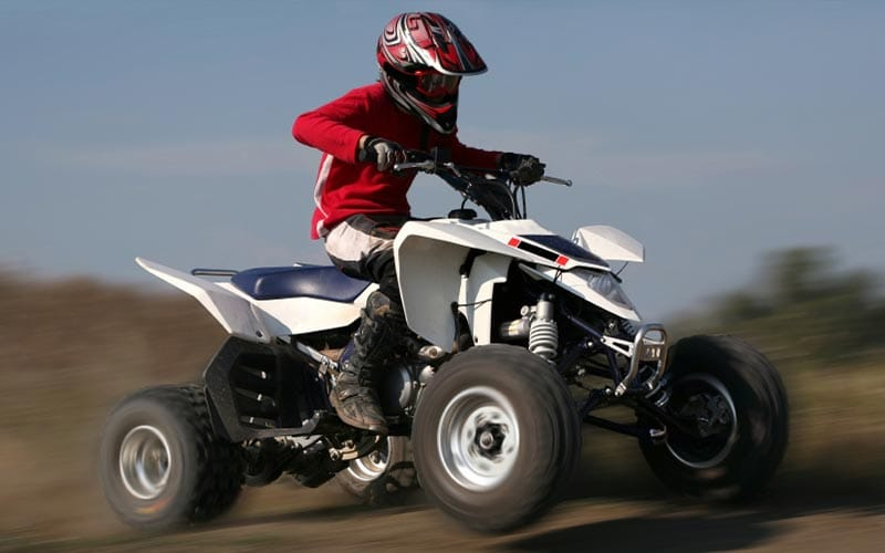 A man riding a quad bike so fast that the background is blurred