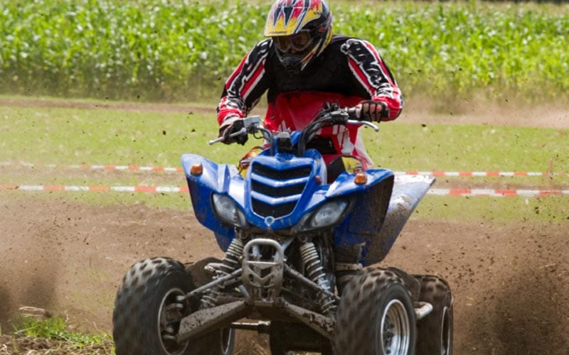A man riding a quad bike through the mud