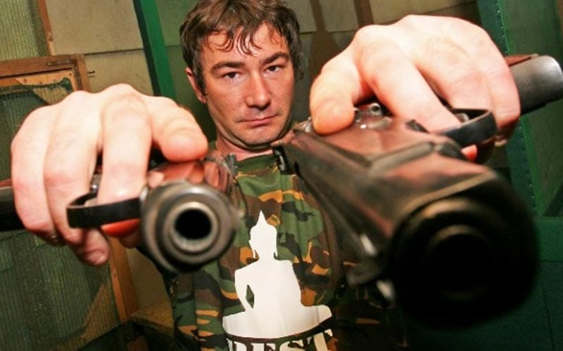 A man holding two guns into the camera