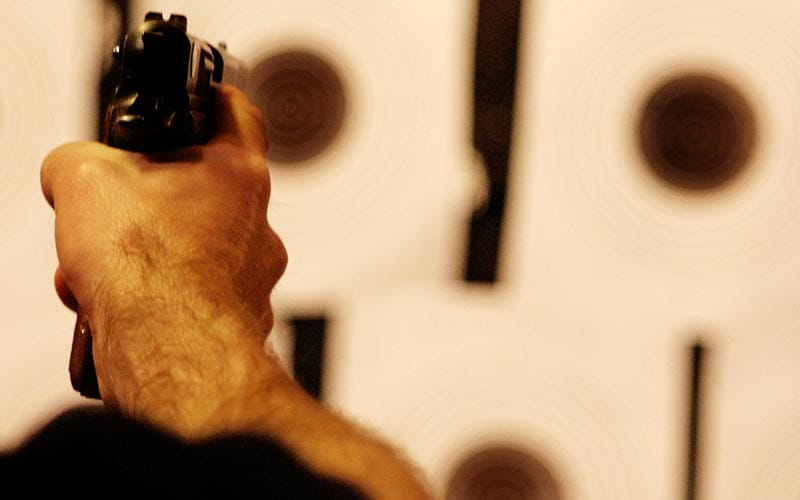 A person's hand firing a gun at some targets
