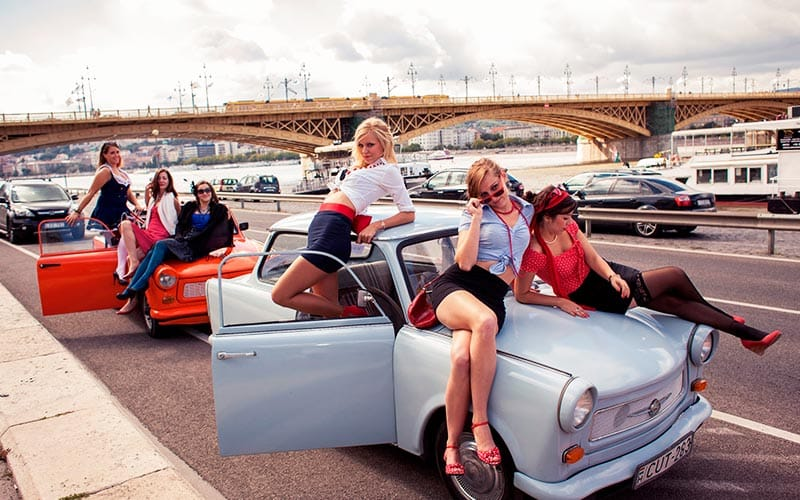 Some women lying on a blue Trabant car