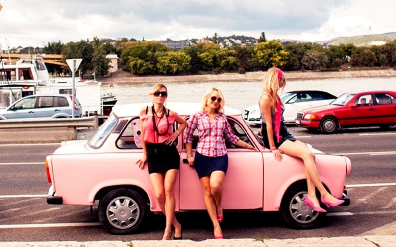 Some women leaning on a pink Trabant