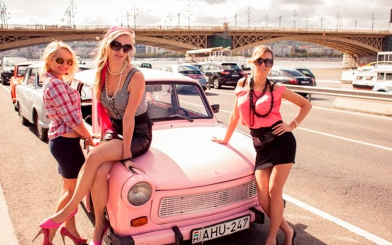 Three women leaning against a Trabant car