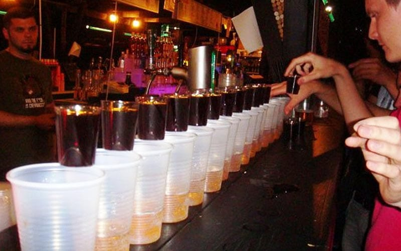 Some glasses lined up on a bar, about to have Jager shots poured into them
