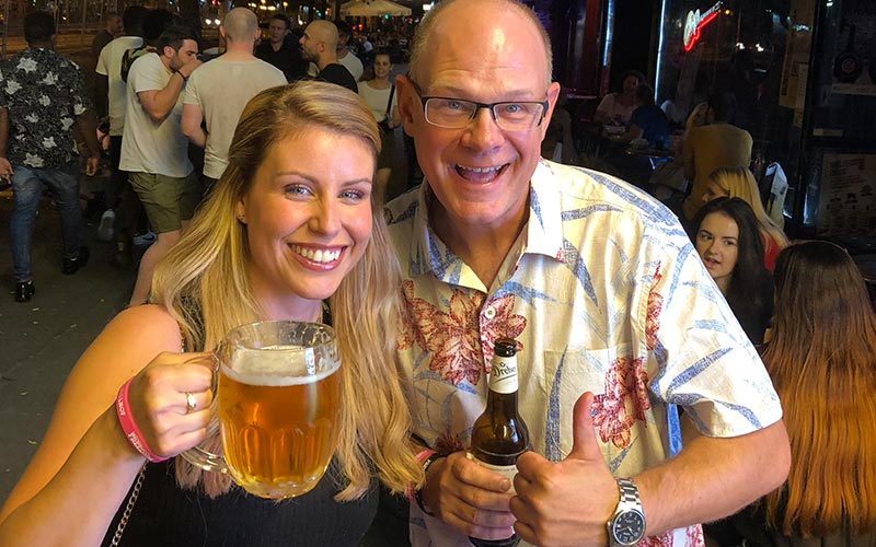 A man with a bottle of beer next to a woman with a pint