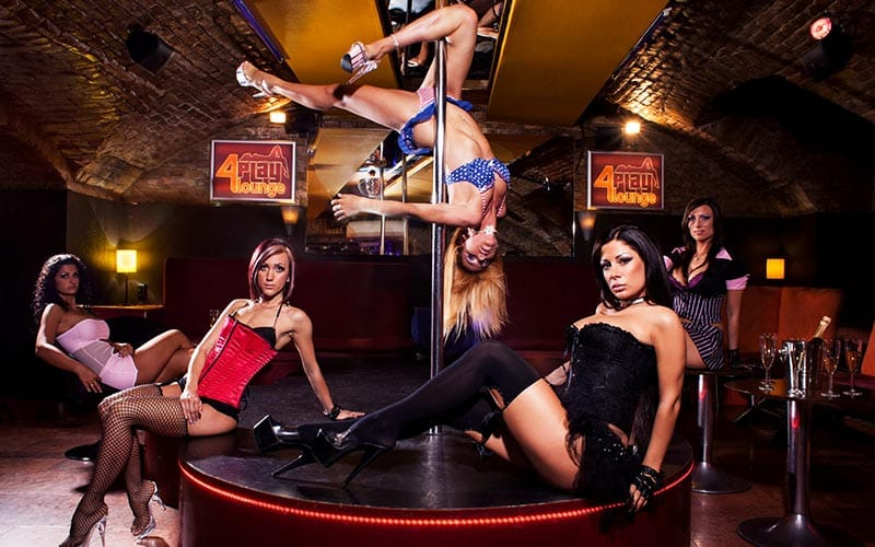 Some strippers posing and one wrapped around a pole