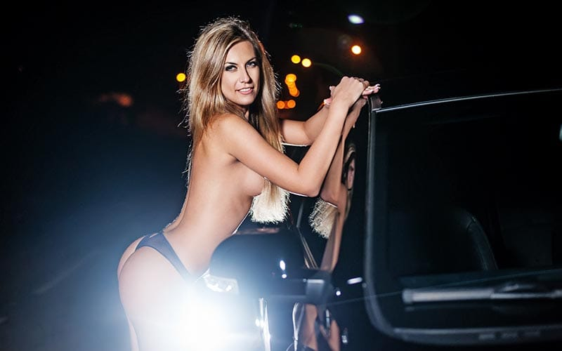 A woman leaning against a car wearing only knickers